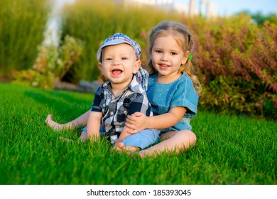 happy sister and brother laughing in the park