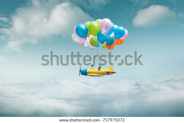 Happy sister enjoy with fantasy plane fly  and floating in sky with bunch of colorful balloons .