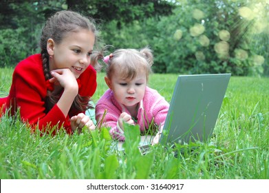 Happy sisters with laptop on the meadow