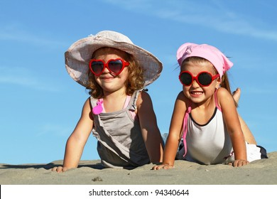 Happy sisters posing with sunglasses on the beach