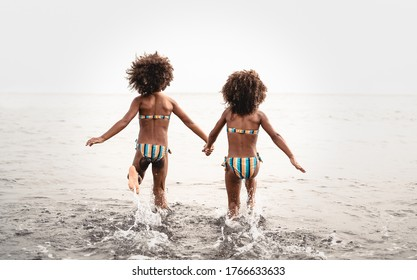 Happy sisters running inside water during summer time - Afro kids having fun playing on the beach - Family love and travel vacation lifestyle concept