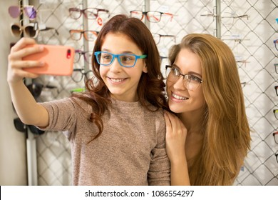 Happy sisters taking selfies together at the eywear store using smart phone. Beautiful happy woman smiling posing for selfies with her adorable little sister wearing glasses at optometrists store