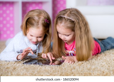 Happy sisters using tablet computer