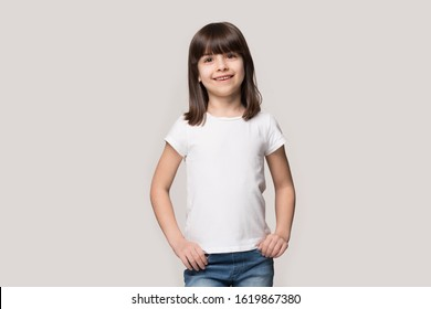 Happy six years old adorable girl in white mock up blank t-shirt on grey studio background. Portrait of smiling fringe hairstyled little cutie, holding hands in jeans pocket, looking at camera, Z