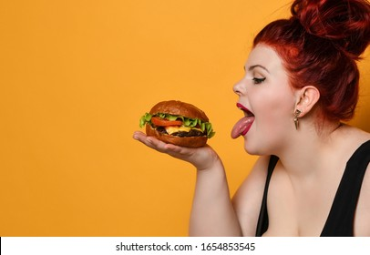 Happy size-plus overweight fat woman happy hold burger cheeseburger sandwich with beef on yellow background. Healthy eating diet fast food concept