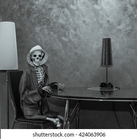 Happy skeleton sitting behind the table in dark dramatic room environment, wearing leather jacket and white hat and waiting for Halloween party
