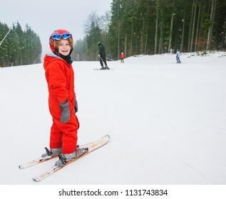 happy skier boy in a winter ski resort, skiing, winter sport, little boy skier portrait with helmet and his snow gear at winter holiday.