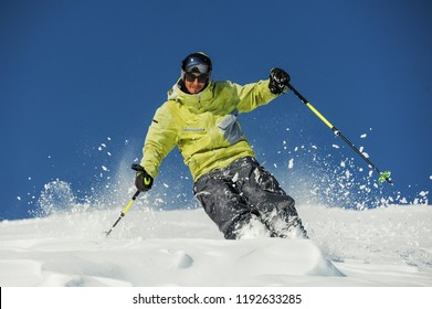Happy skier dressed in bright yellow sportswear riding down the mountain slope in Georgia, Gudauri on sunny day