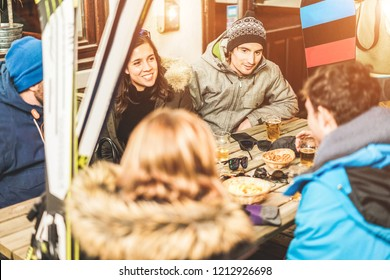 Happy skier friends drinking beers at chalet pub restaurant in mountain on evening time - Young people having fun in winter vacation - Friendship, sport and youth concept - Focus on top right man face