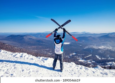 Happy skier man holding pair of skis background snowy mountains, concept sport active winter banner.
