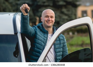 Happy slav or russian man showing the key of his new car