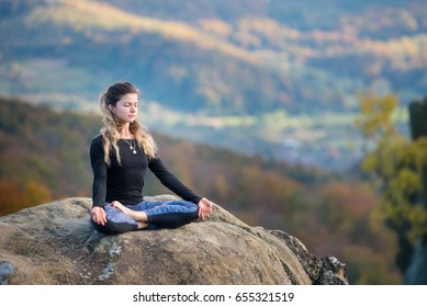 Happy slim girl is practicing yoga and doing asana Siddhasana on the top of the mountain. Autumn forests, rocks and hills on the background