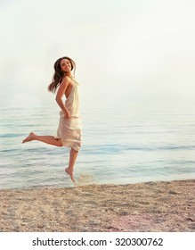 Happy slim woman dressed in white dress jumping against sea backdrop.