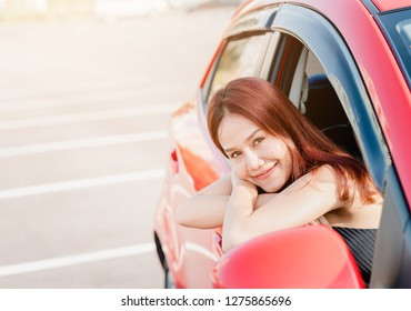 Happy smaile Asian woman driver in red car