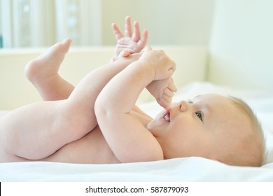happy small baby playing with his legs, and sucking her Toes