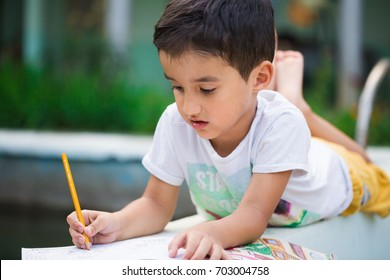 Happy small boy lying on stomach barefoot by the garden pool, smiling, drawing on sketch book with pencil, back to school, preschool activities, quality time at home, kindergarten