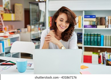 Happy small business manager working on laptop in bookstore