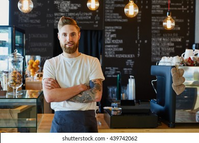 Happy small business owner standing at coffee shop