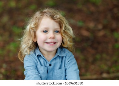 Happy small child with long blond hair enjoying the nature