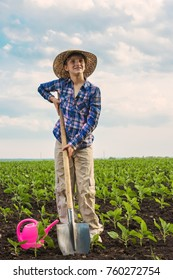 Happy small farmer with spade and watering can in spring field gardening