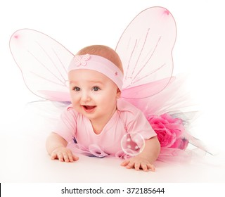 Happy small girl butterfly wings plays on the floor on a background