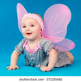 Happy small girl butterfly wings sitting on the floor on a blue background