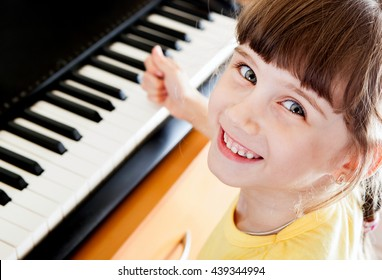 Happy Small Girl with the Piano Keyboard