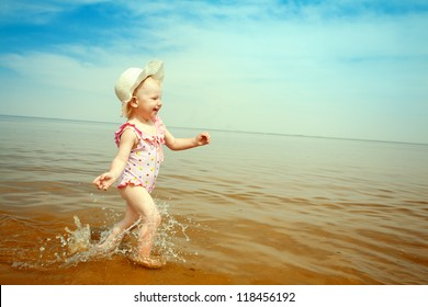 happy small girl running on the beach