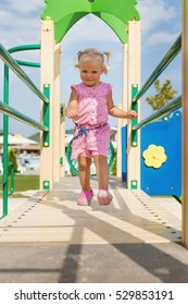 Happy small girl running on outdoor playground equipment