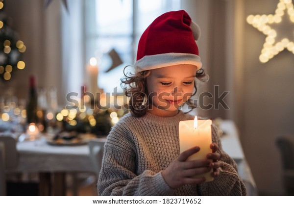 Happy small girl standing indoors at Christmas, holding candle.