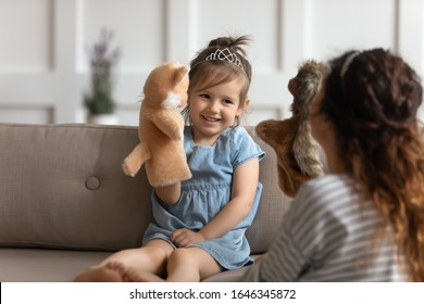 Happy small preschool kid girl sitting on couch, wearing crown, playing with nanny. Playful little child daughter holding fluffy toy, having fun with devoted young mommy at home, childcare concept.