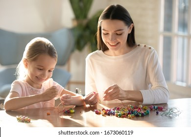 Happy small preschool kid girl sitting at table with elderly sister, creating handmade bracelets with wooden supplies at home. Smiling young mom nanny stringing beads on needles with little daughter.