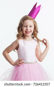 Happy small princess girl in pink dress and crown isolated on white background