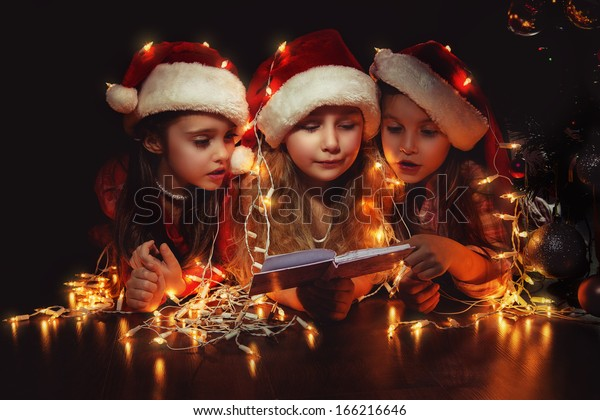 Happy small three girls in Santa hats have a Christmas