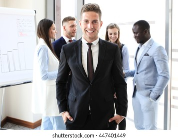 Happy smart business man with team mates discussing in the background