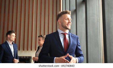 Happy smart business man with team mates discussing in the background.