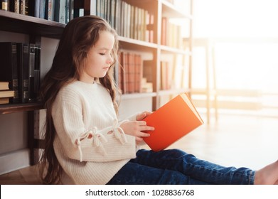 happy smart schoolgirl reading books in library or at home. Kids early learning and education concept.