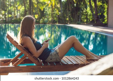 Happy smartphone woman relaxing near swimming pool. Beautiful girl using her mobile phone app 4g data to play songs while relaxing on summer luxury vacations.