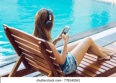 Happy smartphone woman relaxing near swimming pool listening with earbuds to streaming music. Beautiful girl using her mobile phone app 4g data to play songs while relaxing on summer luxury vacations.