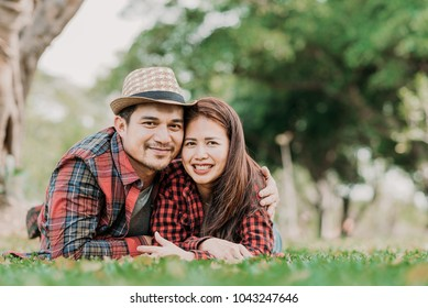 Happy smile Asian couple is lying on green grass having a good time together