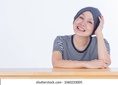 Happy smile cancer patient sit on the table after recovering of chemotherapy, hair fall down use headscarf, smile with photographer her friend/ isolated background