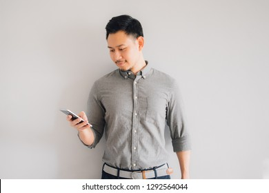 Happy smile face of handsome Asian man use smartphone stand isolated on gray background.