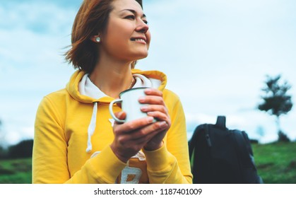 Happy smile girl holding in hands cup of hot tea on green grass in outdoors nature park, beautiful young woman hipster enjoy drinking cup of coffee, lifestyle relax recreation meditation concept