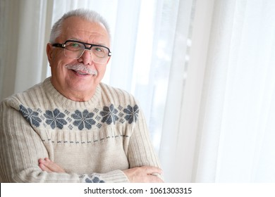 Happy and smile Senior man in glasses 70-75 years old, standing by window with armcross