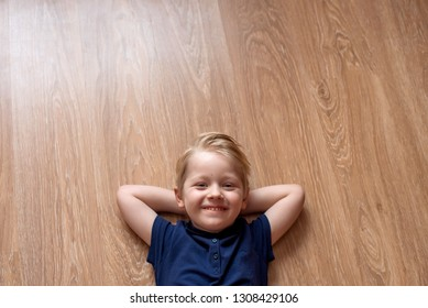 Happy smiled kid laying on brown floor at home. Copy space. Place for text