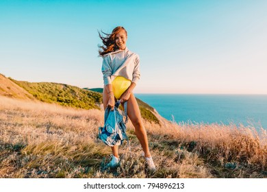 Happy smiled woman outdoor at warm sunset. Happy holiday in the mountains