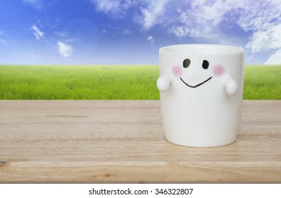 happy smiley face cup on wood table