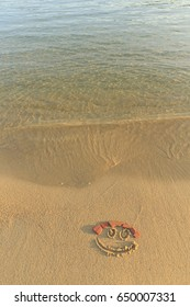 Happy smiley face drawn on sand, Soft sea wave in motion, Beautiful fine sandy beach with smiley face