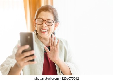Happy smiley face senior woman using smartphone video call camera and talking with her family.Video chat and Technology concept.