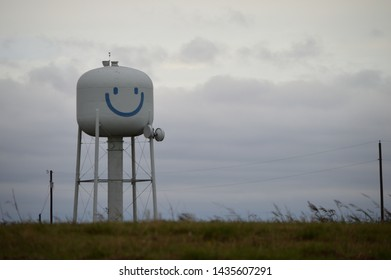 Happy, smiley face water tower in field on a cloudy day.